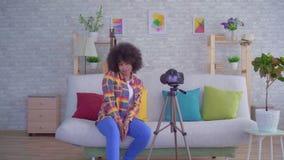 Blogger africain de femme avec une coiffure Afro avant la caméra clips vidéos