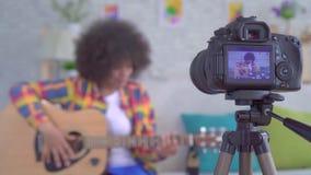 Blogger africain de femme avec une coiffure Afro avec une guitare la vue par l'écran de caméra banque de vidéos