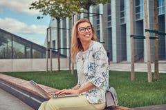 Blogger alla moda di modo facendo uso del computer portatile per lavoro mentre sedendosi fuori su un banco contro un grattacielo Fotografia Stock Libera da Diritti