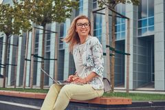 Blogger alla moda di modo facendo uso del computer portatile per lavoro mentre sedendosi fuori su un banco contro un grattacielo Fotografie Stock