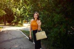 Blogger, biznesowa kobieta z pastylką i torba w ręce dla spaceru w parku, zdjęcia stock