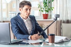 Blogger businessman recording vlog video in office. Concept of social marketing and business training. Blogger man businessman recording vlog video in office royalty free stock photos