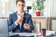Blogger businessman recording vlog video in office. Concept of social marketing and business training. Blogger man businessman recording vlog video in office royalty free stock photography