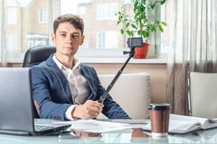 Blogger businessman recording vlog video in office. Concept of social marketing and business training. Blogger man businessman recording vlog video in office stock image