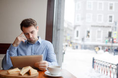 Blogger in cafe. Contemporary entrepreneur with touchpad having lunch break in cafe Stock Photography