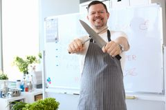 Blogger Chef Sharpening Steel Knife Photography. Culinary Man Whetting Blade of Kitchenware Manually. Healthy Lettuce for Salad. Attractive Male Standing in royalty free stock photo