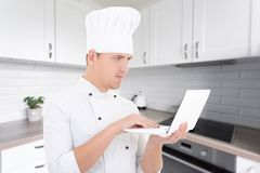 Blogger concept - young man chef in uniform with laptop in moder Stock Images