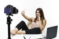 Blogger Concepts. Cheerful Caucasian Female Vlogger Making Selfie on Cellphone For Blog. Isolated Against White. Posing with Legs. On Table in Studio royalty free stock photography