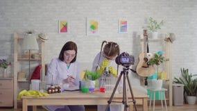 Blogger da mulher e do adolescente, conduzindo uma experiência que olha através de um microscópio em um laboratório químico, uma  video estoque