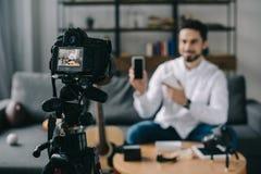 blogger da tecnologia que aponta no smartphone novo com câmera foto de stock