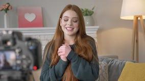 Blogger dai capelli rossi giovane della ragazza, sorridendo, felice, parlando alla macchina fotografica, comodità domestica nei p video d archivio