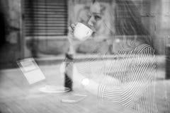 Blogger de femme ayant une boisson et travaillant avec la technologie Photos stock