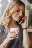 Blogger de femme ayant une pause-café et parlant à son téléphone Image stock