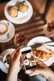 Blogger de la comida con el teléfono Desayuno para dos: cruasán con el jamón, café, bebida de restauración Foto de archivo libre de regalías