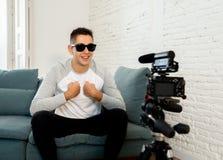 Blogger del giovane che registra un video nel flusso continuo sulla macchina fotografica per i seguaci su Internet immagine stock