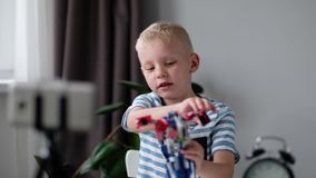 Blogger del niño pequeño con vídeo y mostrar de la grabación del teléfono móvil de la cámara sus juguetes en casa El bloguear, vi almacen de video
