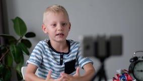 Blogger del niño pequeño con vídeo y mostrar de la grabación del teléfono móvil de la cámara sus juguetes en casa El bloguear, vi almacen de metraje de vídeo