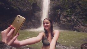 Blogger del viaje de la mujer joven que hace la foto del selfie al teléfono móvil en fondo de la cascada de la montaña Tiroteo so almacen de video