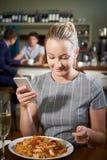 Blogger dell'alimento che invia rassegna online del pasto del ristorante facendo uso di Mobi fotografie stock libere da diritti