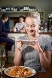 Blogger dell'alimento che prende immagine del pasto del ristorante sul telefono cellulare fotografia stock libera da diritti