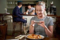 Blogger dell'alimento che prende immagine del pasto del ristorante sul telefono cellulare immagini stock