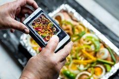 Blogger dell'alimento tramite lavoro - la persona sta fotografando un alimento con uno smartphone immagine stock libera da diritti