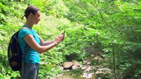 Blogger della donna che fa la foto del selfie dallo smartphone con il fondo tropicale verde della foresta della montagna stock footage
