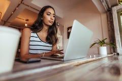 Blogger della donna sul lavoro sul suo computer portatile fotografia stock libera da diritti