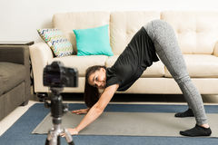 Blogger demonstrating yoga pose on video. Good looking young fitness and yoga blogger giving some advice and demonstrating a pose on video Royalty Free Stock Photos