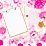 Blogger der Freiberuflerzusammensetzung Arbeitsplatz mit Klemmbrett, Notizbuch, Stift und rosa Rosen auf weißem Hintergrund Flach Stockfotografie