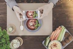 Blogger, der gesundes Lebensmittel des strengen Vegetariers fotografiert Stockbilder