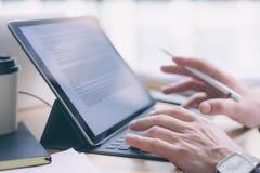 Blogger, der am Studio arbeitet Nahaufnahmeansicht von den männlichen Händen, die auf elektronischer Tablettentastaturdockstation Stockfotografie