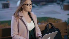 Blogger di bellezza della donna facendo uso del computer portatile che si siede sul banco nel parco della città video d archivio