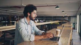 Blogger die aan laptop in cafetaria werken stock footage