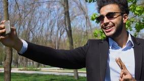 Blogger die video op nieuwe telefoon en het beduimelen tonen omhoog en het teken van de vredesvinger in langzame motie maken stock videobeelden