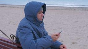 Blogger do homem em um azul abaixo do revestimento que senta-se em um banco na praia da areia e que escreve um cargo em meios soc video estoque