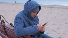 Blogger do homem em um azul abaixo do revestimento que senta-se em um banco na praia da areia e que escreve um cargo em meios soc filme