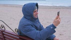 Blogger do homem em um azul abaixo do revestimento que senta-se em um banco na praia da areia e que fala um bate-papo video no te filme