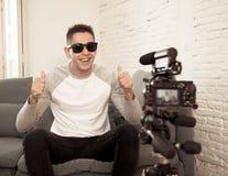 Blogger do homem novo que grava um vídeo na fluência na câmera para os seguidores no Internet imagem de stock royalty free