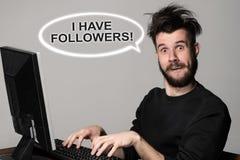 Blogger engraçado e louco que usa um computador Fotos de Stock