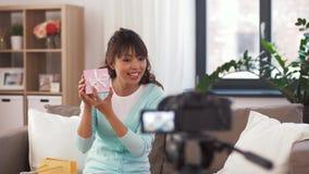 Blogger féminin asiatique avec la vidéo de enregistrement de sac de cadeau banque de vidéos