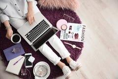 Blogger féminin avec l'ordinateur portable et la tasse de café d'intérieur photographie stock libre de droits