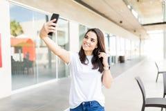 Blogger féminin de sourire prenant Selfie utilisant Smartphone image libre de droits