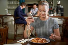 Blogger fêmea do alimento que afixa a revisão em linha da refeição Usi do restaurante fotografia de stock