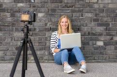 Blogger fêmea louro bonito com vídeo da gravação do portátil Foto de Stock