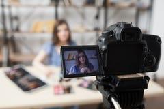 Blogger fêmea novo da beleza na tela da câmera fotografia de stock royalty free