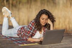 Blogger fêmea que escreve um artigo na natureza foto de stock