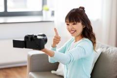 Blogger f?minin asiatique avec la vid?o de enregistrement de cam?ra photos stock