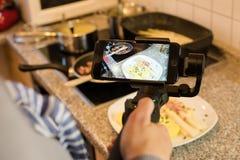 Blogger faisant la vidéo de smartphone tout en préparant un plat d'asperge Photos libres de droits