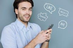 Blogger famoso do Internet que guarda um smartphone moderno e que olha seguro imagem de stock royalty free